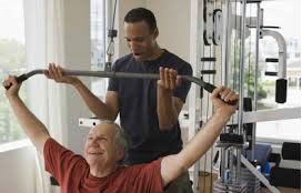 """Current sophomore Corey Matthews assists Mr. Bombe with his daily workout in the Fitness Center on campus. """"It's like I never left!"""" declared Mr. Bombe about the campus. Photo Credit: stockphoto.com"""