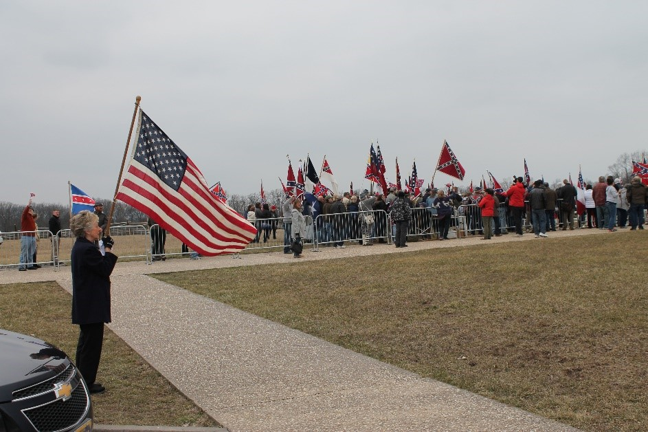 One woman stood between the two barricades holding her father's burial flag. Photo credit to the author.