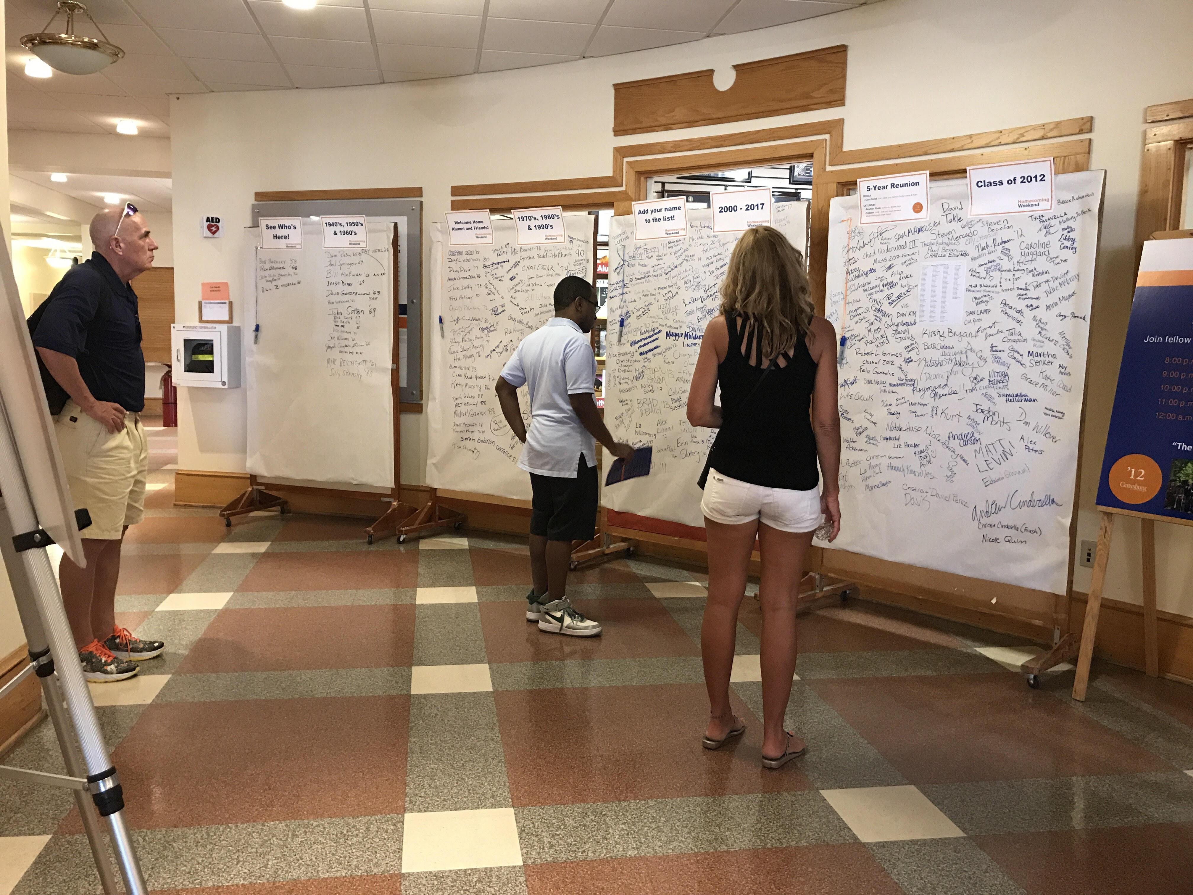 Alumni take a look at sign-in sheets in the College Union Building at Homecoming (Photo Maddie Neiman / The Gettysburgian)