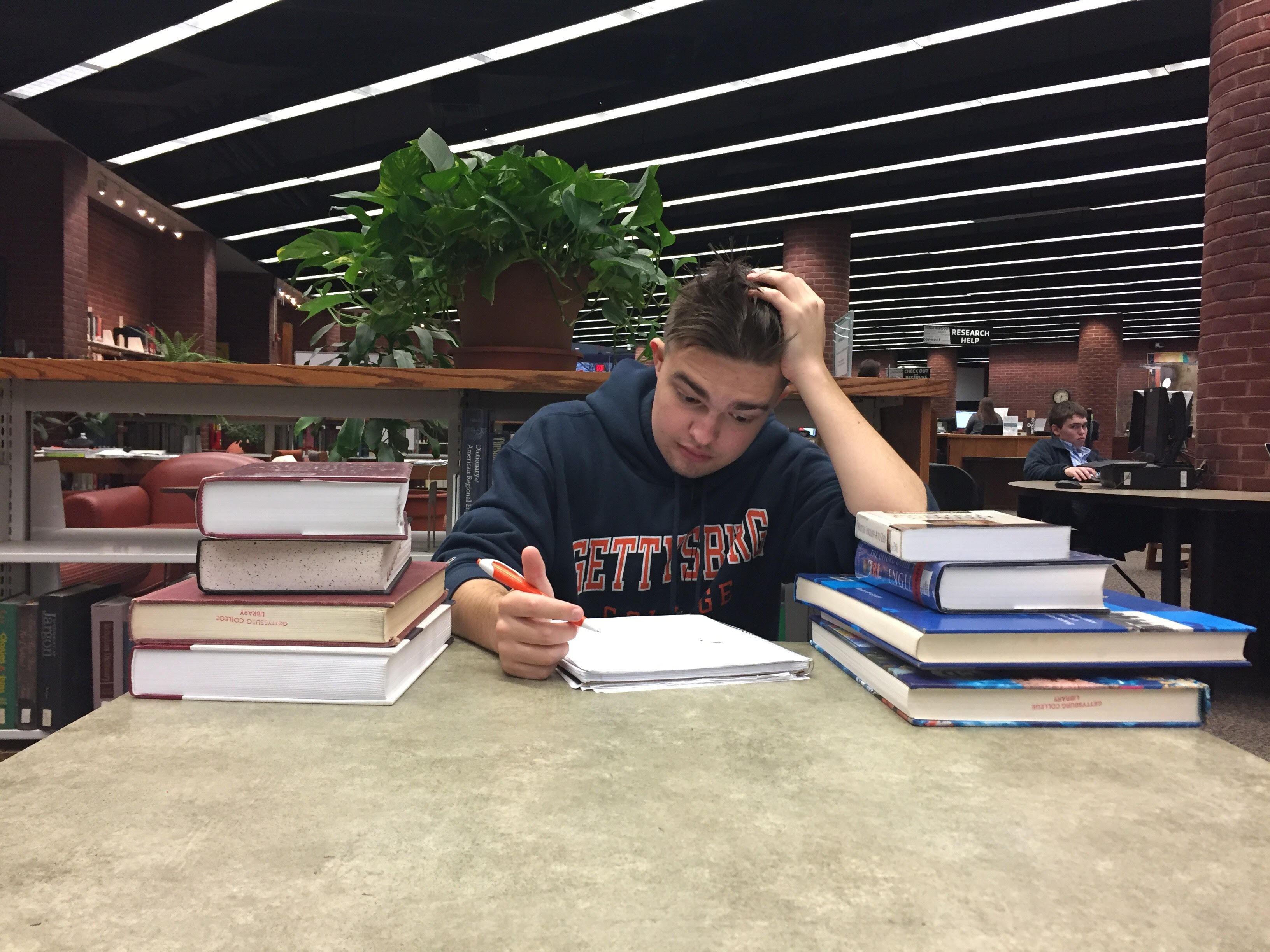 Max Glover '21 with a stack of textbooks in Musselman Library (Photo Gauri Mangala / The Gettysburgian)