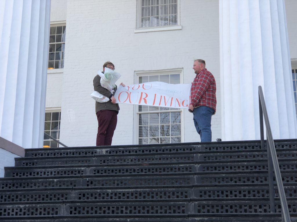 Sam Weathers '18 and James Goodman '20 try to keep their banners from blowing in the strong winds shortly after 11 a.m Friday morning. (Photo Jamie Welch/The Gettysburgian)