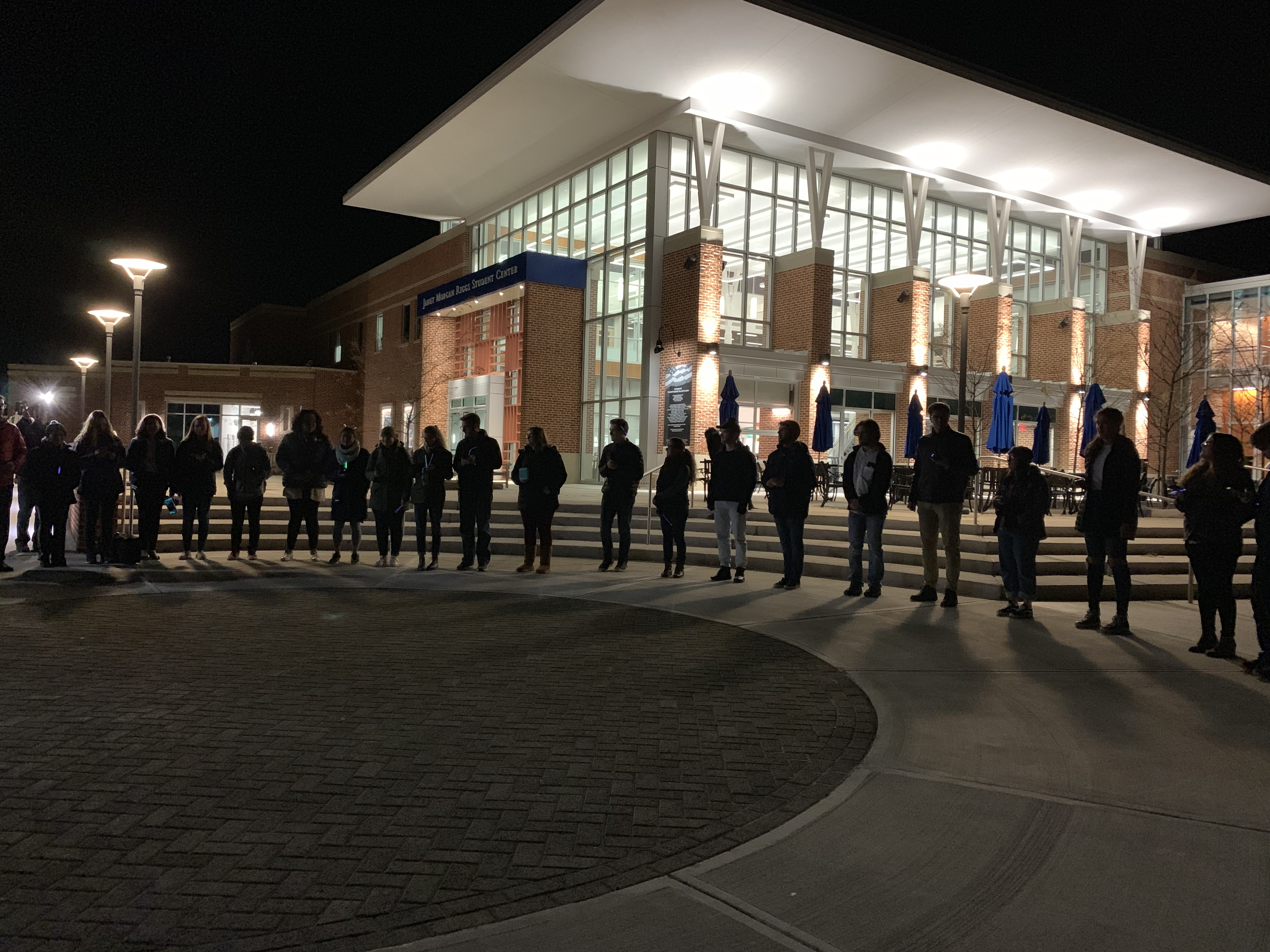 Unsilent Night participants form a circle outside of the College Union Building after walking across campus with music playing from their mobile devices (Photo courtesy of Julia Sharapi)