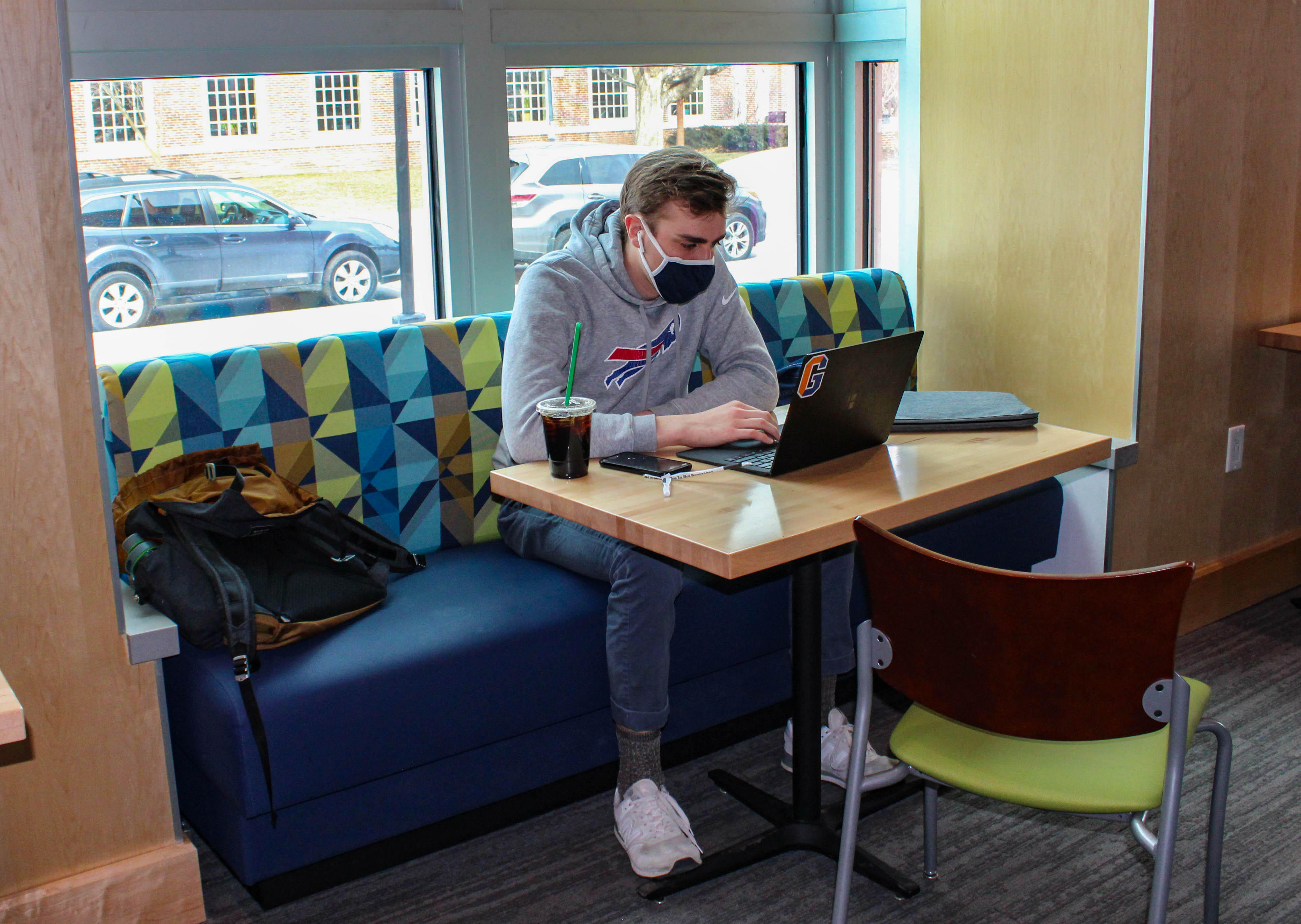 Daniel Janzow '21 does homework in the Junction. Despite the area's reduced capacity, students still enjoy eating meals and doing work here. (Photo Mary Frasier/The Gettysburgian)