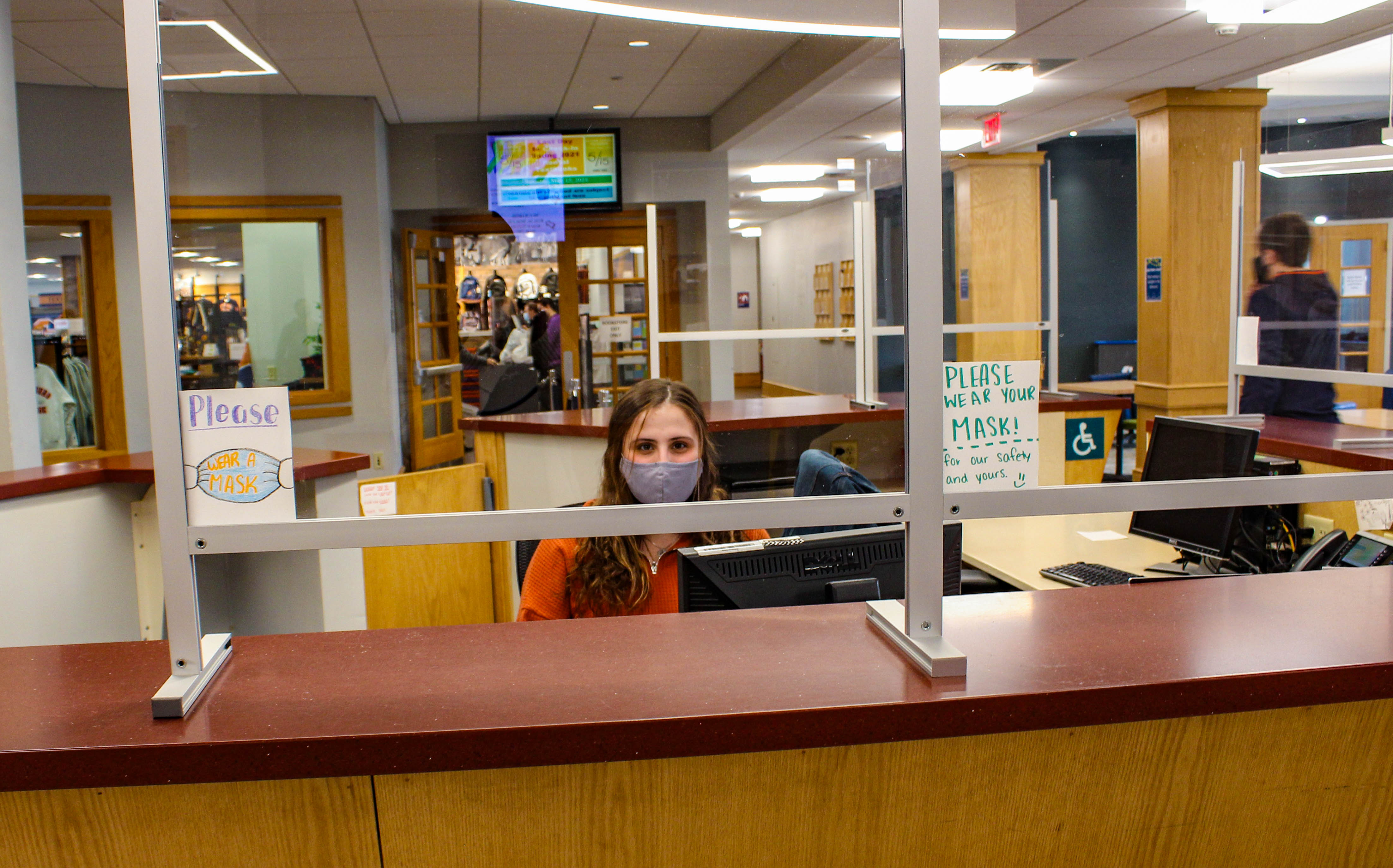 Hannah Lindert '22 works her shift at the CUB desk. Plastic dividers like the ones pictured above help are measures implemented with the goal of reducing the spread of COVID-19 on campus. (Photo Mary Frasier/The Gettysburgian)