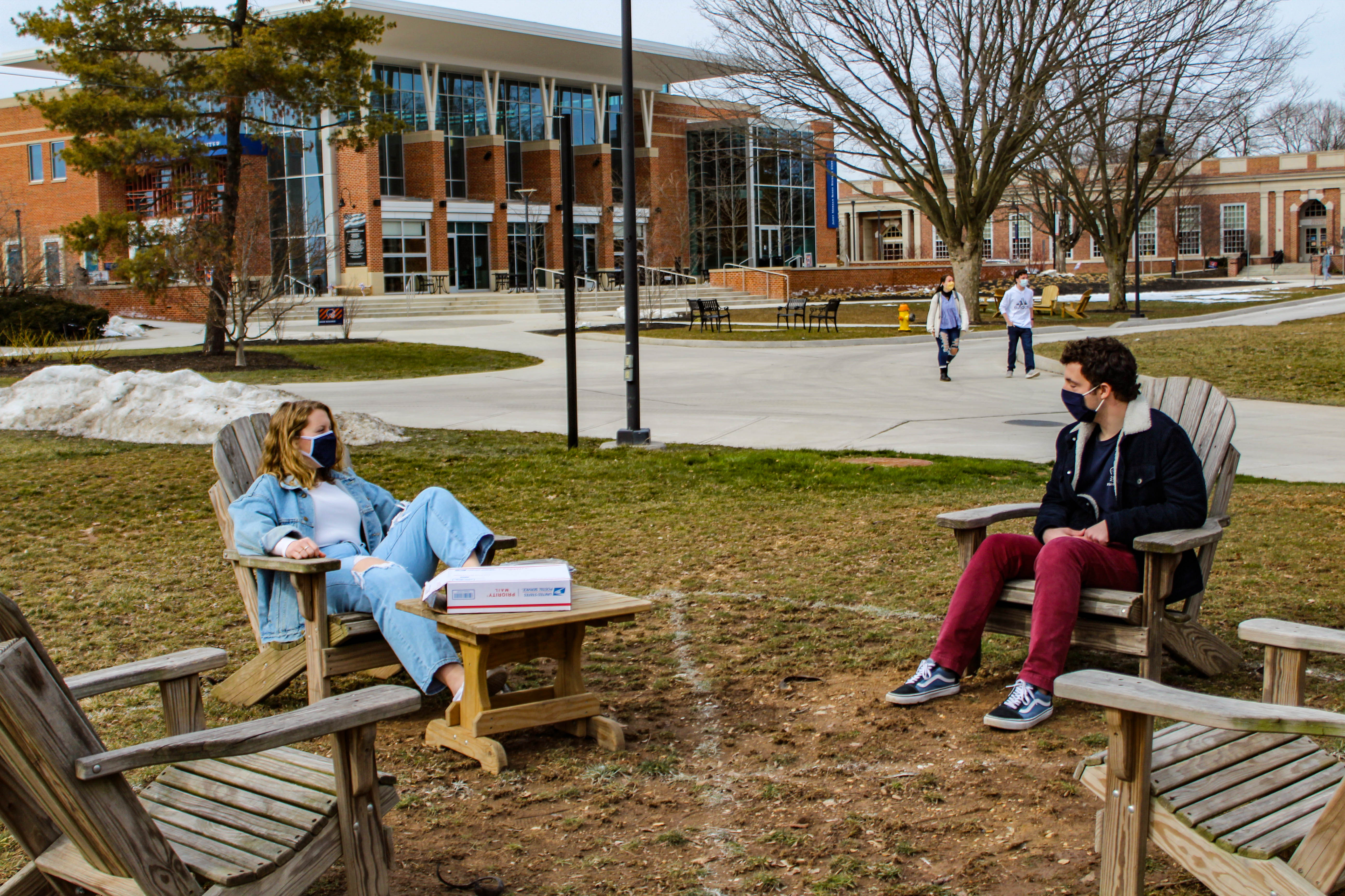 Rachel Wert '21 and Timothy Wilson '21 lounge in adirondack chairs on Stine Lake. In order to enforce social distance rules, the chairs are situated six feet apart from each other. (Photo Mary Frasier/The Gettysburgian)