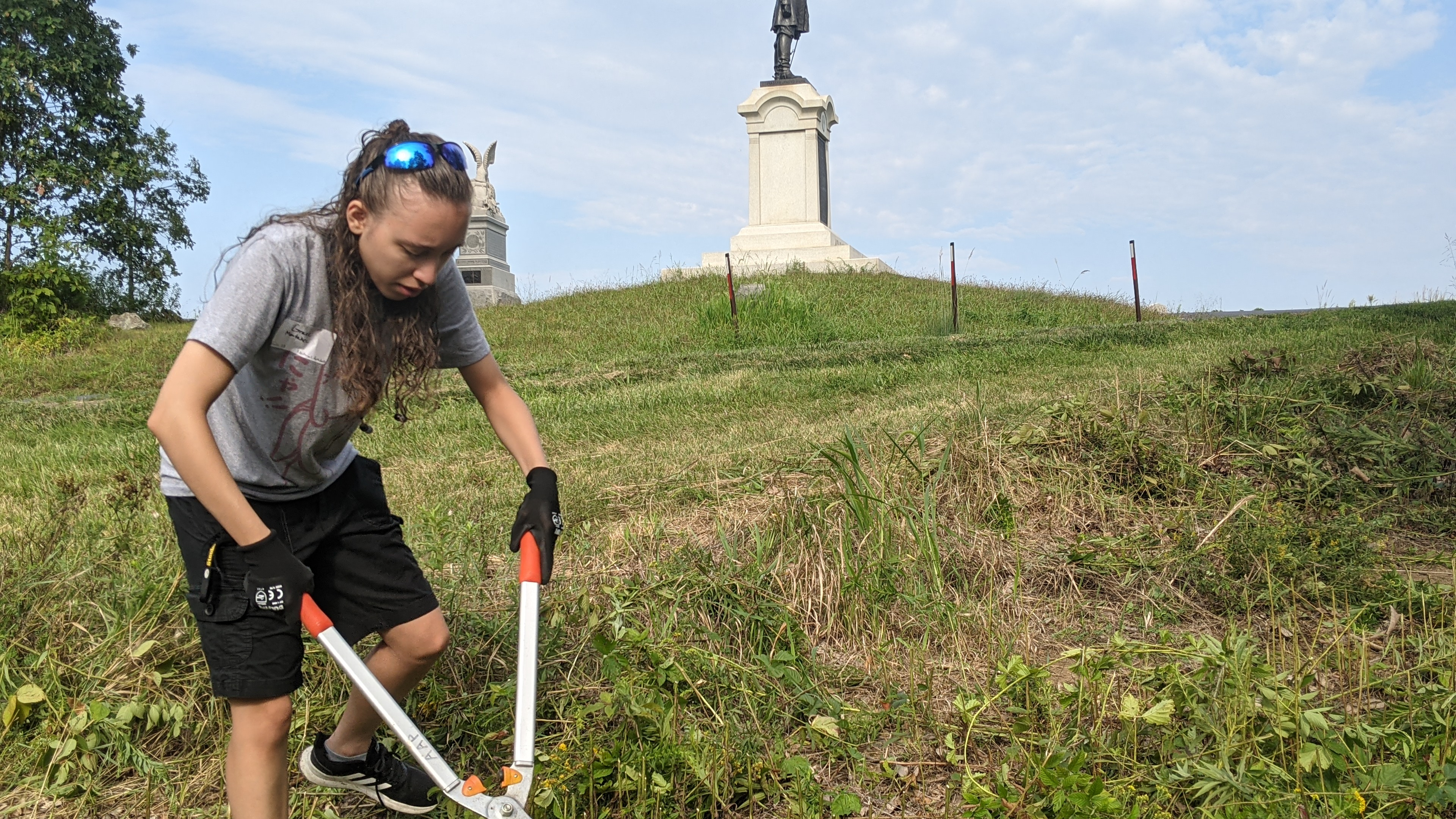 A student cuts down the brush near a monument (Photo Maggie Galloway/The Gettysburgian)